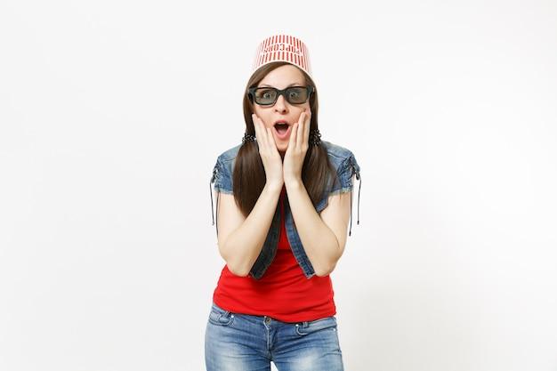 Portrait d'une jeune femme séduisante choquée dans des lunettes 3d et des vêtements décontractés avec un seau pour du pop-corn sur la tête en regardant un film et en s'accrochant au visage isolé sur fond blanc. les émotions au cinéma.