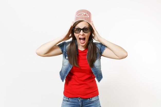 Portrait d'une jeune femme séduisante choquée dans des lunettes 3d et des vêtements décontractés avec un seau pour du pop-corn sur la tête en regardant un film et s'accrochant à la tête isolée sur fond blanc. les émotions au cinéma.