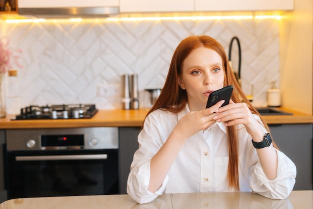 Portrait d'une jeune femme séduisante enregistrant une réponse par message audio dans un réseau social pour un ami