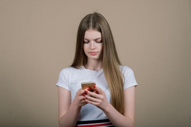 Portrait de jeune femme séduisante faisant selfie photo sur smartphone isolé sur fond blanc