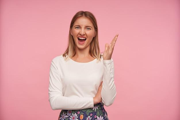 Portrait de jeune femme séduisante joyeuse à la recherche d'appareil photo avec une grande bouche ouverte et fronçant les sourcils, levant la main tout en posant sur fond rose dans des vêtements décontractés
