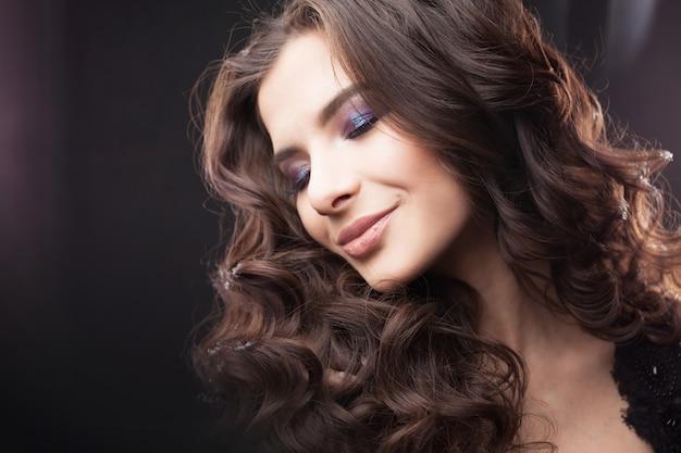 Portrait d'une jeune femme séduisante avec de magnifiques cheveux bouclés. jolie brune.