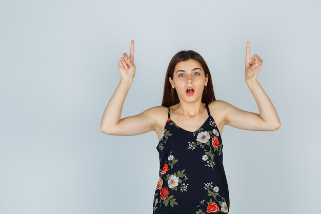 Portrait d'une jeune femme séduisante pointant vers le haut en chemisier et regardant la vue de face se demande