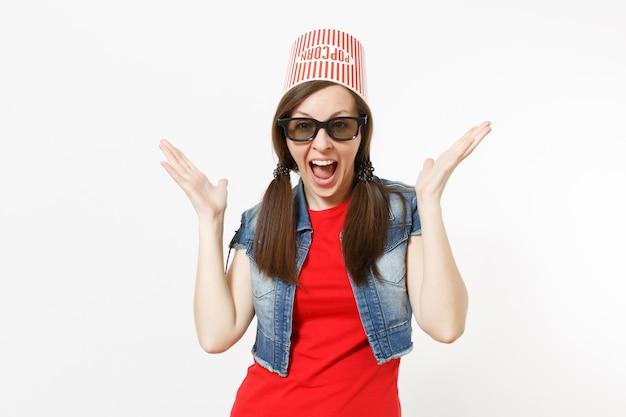 Portrait de jeune femme séduisante ravie dans des lunettes 3d et des vêtements décontractés avec un seau pour du pop-corn sur la tête en regardant un film et en écartant les mains isolées sur fond blanc. les émotions au cinéma.
