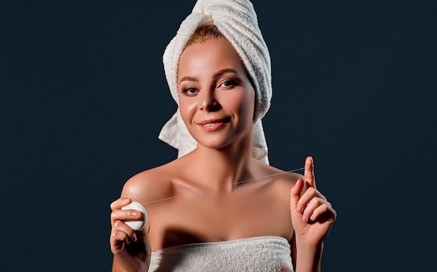 Portrait d'une jeune femme séduisante avec une serviette sur la tête utilise du fil dentaire sur un mur noir.