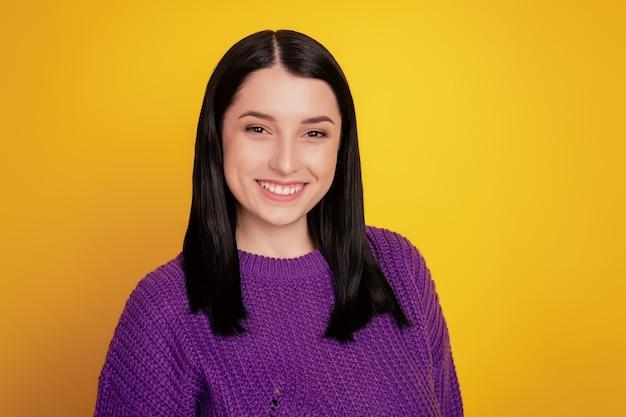 Portrait de jeune femme séduisante sourire positif heureux à la caméra debout mignon pull confiant porter sur fond jaune