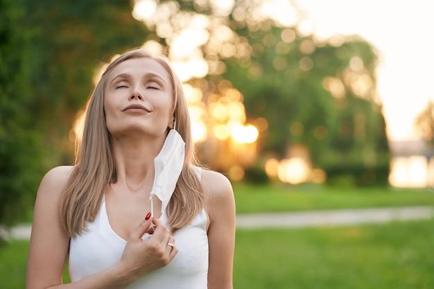 Portrait de jeune femme séduisante avec les yeux fermés en enlevant le masque de protection blanc et en respirant profondément.