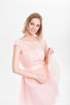 Portrait de jeune femme sensuelle blonde souriante en robe de cocktail rose sur fond gris
