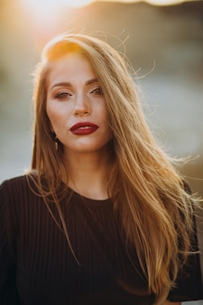 Portrait d'une jeune femme sensuelle sur un coucher de soleil