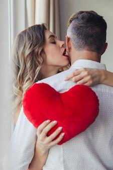 Portrait d'une jeune femme sensuelle tenant son petit ami, concept de la saint-valentin