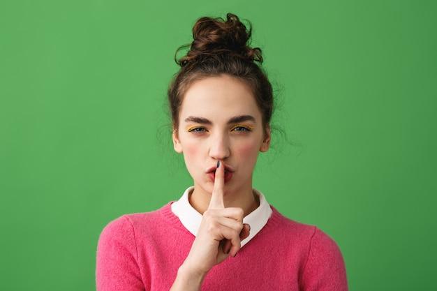 Portrait d'une jeune femme sérieuse montrant le geste de silence isolé sur vert