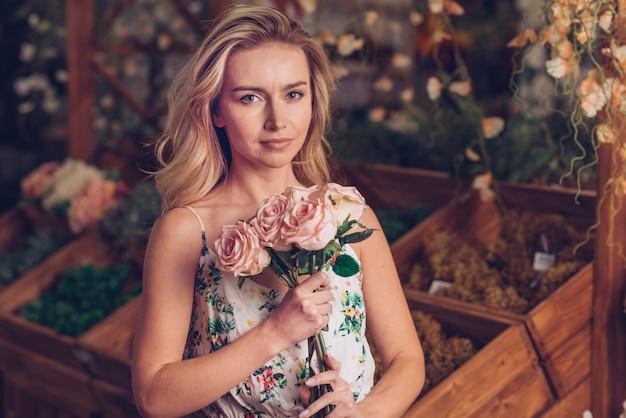 Portrait d'une jeune femme sérieuse tenant des roses roses à la main
