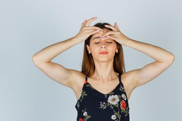 Portrait de jeune femme serrant son bouton sur le front en blouse et à la vue de face détendue