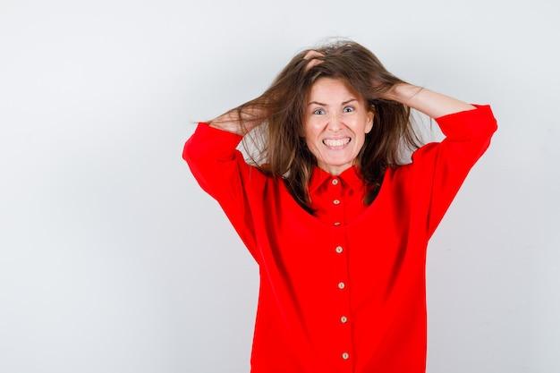 Portrait de jeune femme serrant la tête avec les mains, serrant les dents en blouse rouge et regardant la vue de face excitée