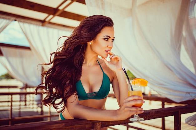 Portrait de jeune femme sexy en bikini avec verre à cocktail orange avec de la paille et des fruits posant au bar en bois de la tente avec des rideaux blancs