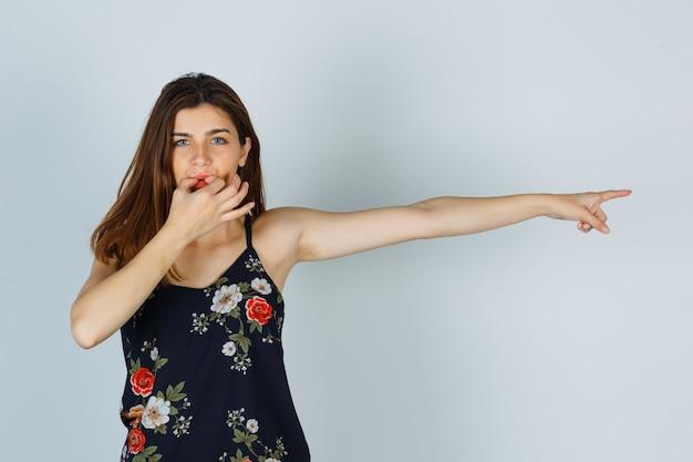 Portrait de jeune femme sifflant avec les doigts, pointant vers le côté