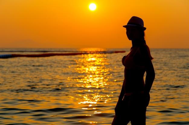 Portrait de jeune femme en silhouette au bord de la mer