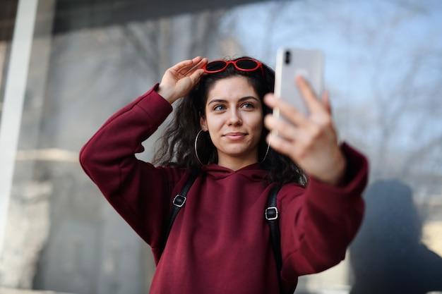 Portrait de jeune femme avec smartphone debout à l'extérieur sur rue en ville, prenant selfie.