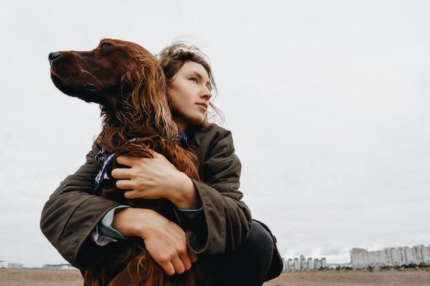 Portrait d'une jeune femme avec son chien. chien setter irlandais dans les bras de la maîtresse aimante.