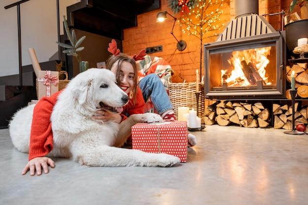 Portrait d'une jeune femme avec son mignon chien blanc en train de déballer des coffrets cadeaux au coin d'une cheminée pendant de joyeuses fêtes de fin d'année à la maison