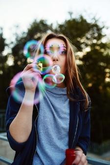 Portrait de jeune femme soufflant des bulles de savon