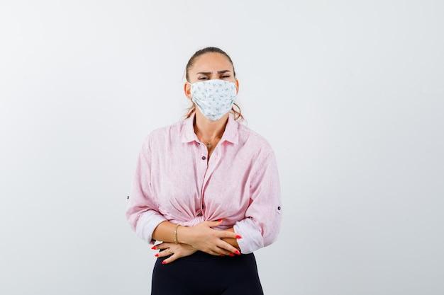 Portrait de jeune femme souffrant de maux d'estomac en chemise, pantalon, masque et à la vue de face douloureuse