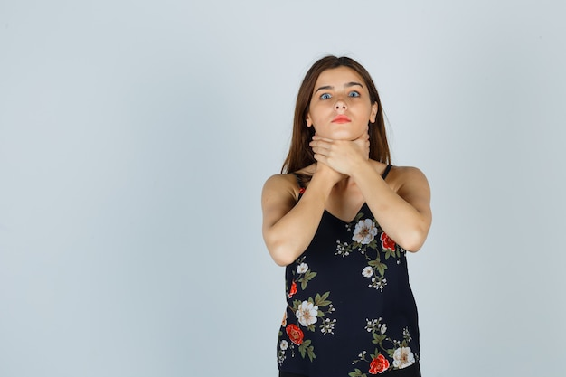 Portrait de jeune femme souffrant de maux de gorge en blouse et à la vue de face malade