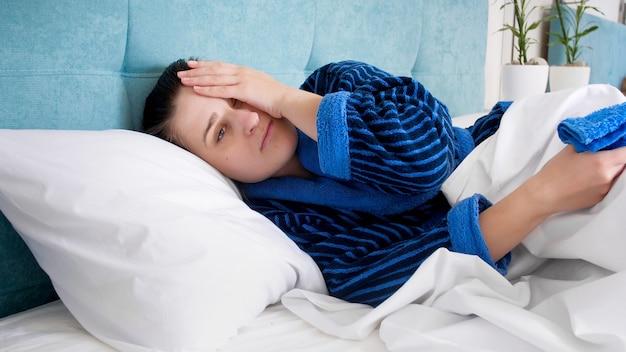 Portrait de jeune femme souffrant de migraine au lit.
