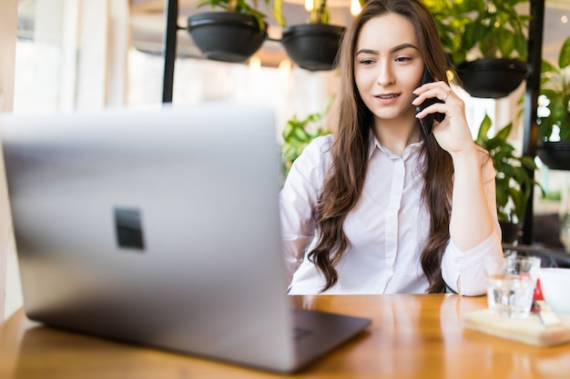 Portrait de jeune femme souriante appelant sa meilleure amie, ayant une pause, racontant quelque chose de drôle, assis dans un café