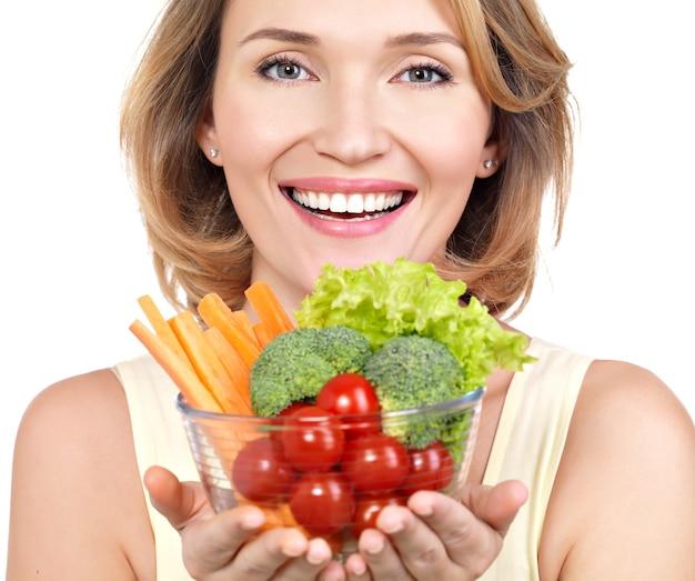 Portrait d'une jeune femme souriante avec une assiette de légumes isolé sur blanc.