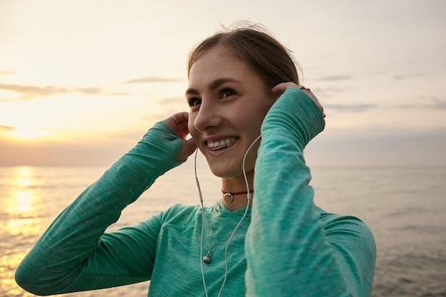 Portrait de jeune femme souriante au bord de la mer le matin, écoutant la musique préférée au casque.
