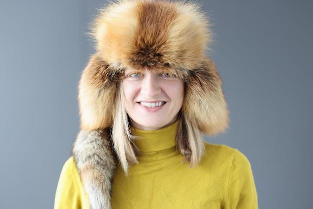 Portrait de jeune femme souriante au chapeau de fourrure d'hiver