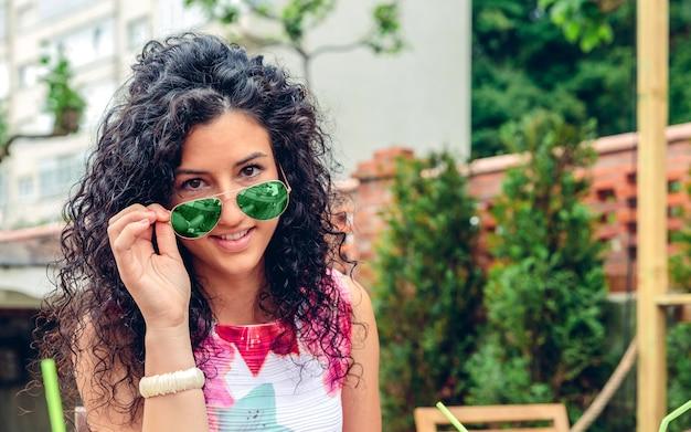 Portrait de jeune femme souriante aux cheveux bouclés regardant la caméra sur des lunettes de soleil bleues à l'extérieur