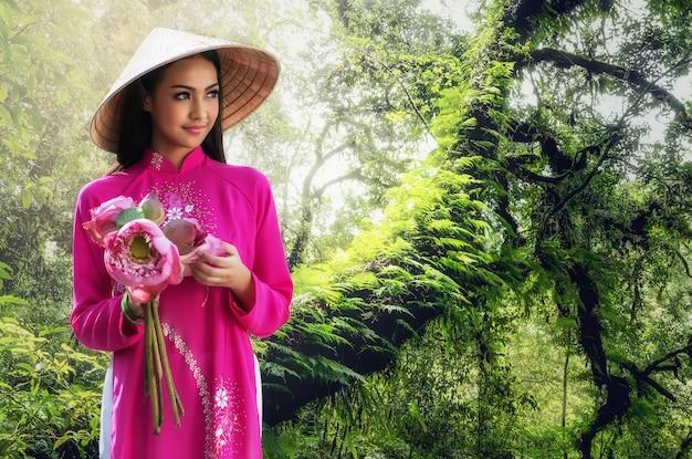 Portrait d'une jeune femme souriante aux cheveux longs portant une robe traditionnelle du vietnam