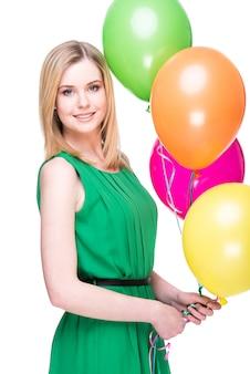 Portrait d'une jeune femme souriante avec des ballons colorés.