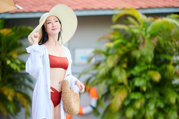 Portrait de jeune femme souriante en bikini, chapeau de paille et chemise blanche debout mouillé après la baignade dans la piscine ou la mer