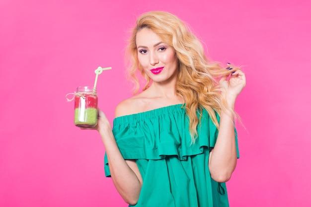 Portrait de jeune femme souriante, boire du jus de smoothie sur fond rose.