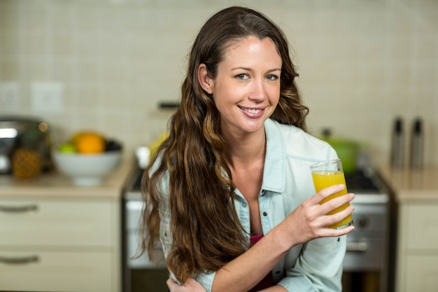 Portrait de jeune femme souriante en buvant du jus