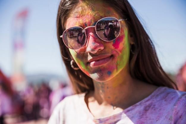 Portrait d'une jeune femme souriante a couvert son visage avec de la poudre de holi
