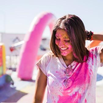 Portrait d'une jeune femme souriante couverte de couleur rose holi