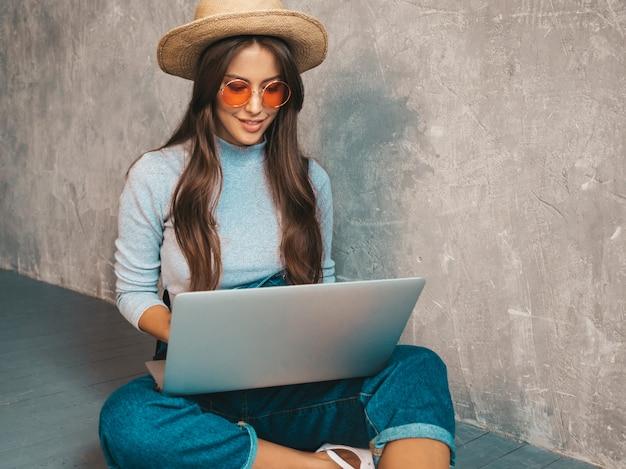 Portrait de jeune femme souriante créative à lunettes de soleil. belle fille assise sur le sol près du mur gris. taper et rechercher des informations