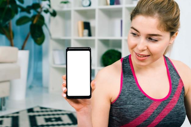 Portrait, de, jeune femme souriante, dans, sportswear, projection, elle, téléphone intelligent, à, écran blanc