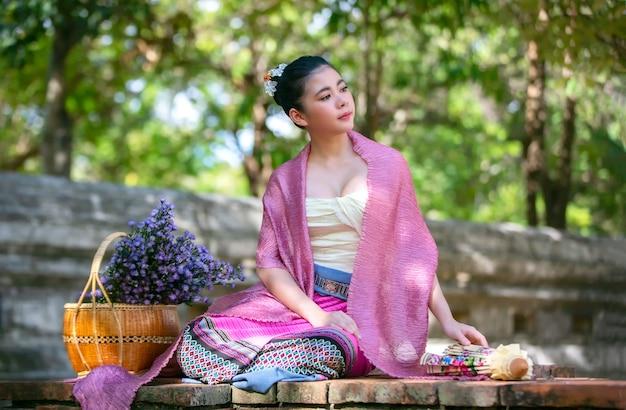 Portrait d'une jeune femme souriante dans des vêtements traditionnels thaïlandais lanna assis devant un panier de fleurs