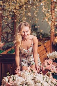 Portrait d'une jeune femme souriante, debout derrière le bouquet de roses