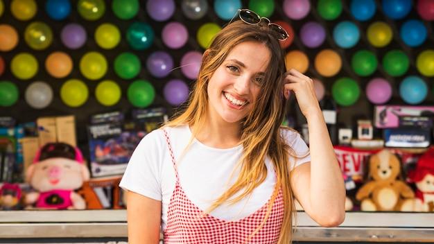 Portrait de jeune femme souriante, debout devant des jouets au parc d'attractions
