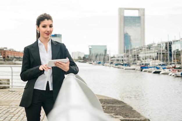 Portrait d'une jeune femme souriante debout près du port