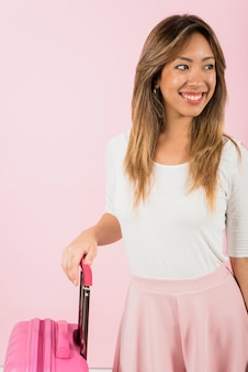 Portrait d'une jeune femme souriante, debout près du sac de bagages sur fond rose