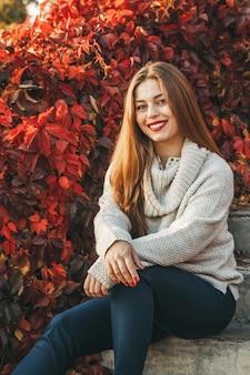 Portrait d'une jeune femme souriante. elle est assise dans les escaliers. les feuilles rouges sont sur le fond.