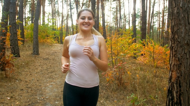 Portrait de jeune femme souriante faisant du sport et du jogging en forêt.