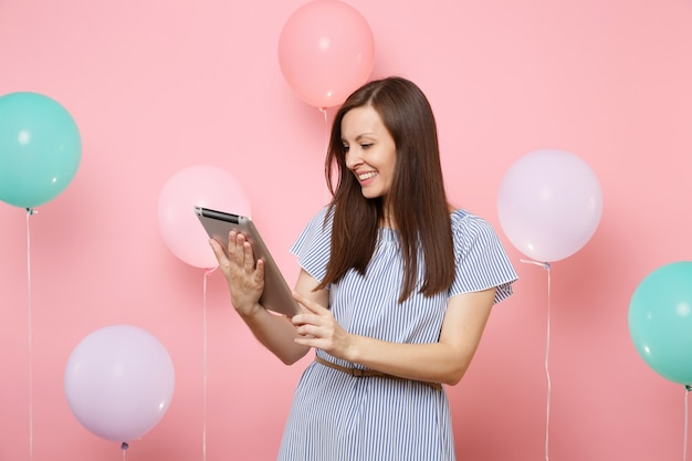 Portrait d'une jeune femme souriante et heureuse portant une robe bleue tenant à l'aide d'un ordinateur tablette sur fond rose pastel avec des ballons à air colorés. fête d'anniversaire, concept d'émotions sincères.